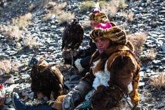 Chasseur kazakh aux lièvres avec l'aigle d'or - Berkutchi, dans les collines de désert de la Mongolie occidentale photos libres de droits