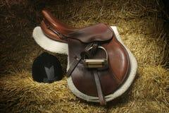 Chasseur/selle de pullover et chapeau de chasse sur des balles de paille Photos stock