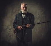 Chasseur supérieur avec un fusil de chasse dans un habillement traditionnel de tir, posant sur un fond foncé Photographie stock