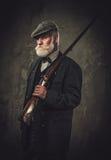 Chasseur supérieur avec un fusil de chasse dans un habillement traditionnel de tir, posant sur un fond foncé Photos stock