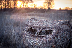 Chasseurs attendant la proie dans la tente de chasse dans les buissons tubulaires à côté de la rivière pendant les levers de sole photos stock