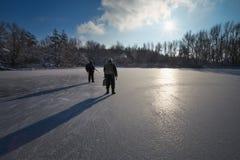 Chasseurs avec des armes sur l'étang de glace photos stock
