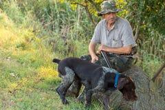 Chasseurs avec une arme à feu et un drathaar allemand Chasse de pigeon avec des chiens S photos libres de droits