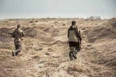 Chasseurs d'hommes courant à travers le champ rural sec pendant la chasse images stock