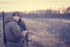 Chasseurs dans le domaine rual pendant la saison de chasse tenant le smartphone image stock