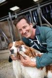 Chasseurs de chien choyant d'agriculteur devant la grange images libres de droits