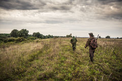 Chasseurs passant par le champ rural avec le ciel dramatique pendant la saison de chasse photographie stock libre de droits