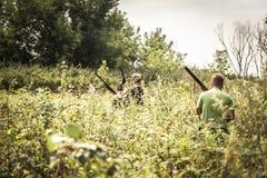 Chasseurs traversant des buissons pendant la saison de chasse dans le jour d'été photographie stock libre de droits