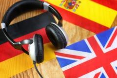 Chassez l'écouteur et le drapeau de langue sur une table Image stock