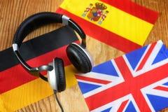 Chassez l'écouteur et le drapeau de langue sur une table Photo libre de droits