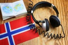 Chassez l'écouteur et le drapeau de langue sur une table Photo stock