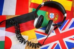 Chassez l'écouteur et le drapeau de langue sur une table Images stock