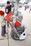 Chassi av ett militärt flygplan Barn på hjulet av chassiet Kämpe Su-35 på flygshowen Flygplan på flygfältet som ska visas Fotografering för Bildbyråer