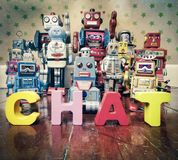Chat bot robots. Chat Bot with wooden letters with retro robot toys on old woden floor Stock Images