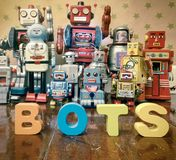 Chat bot robots. Chat Bot with wooden letters with retro robot toys on old woden floor Stock Photo