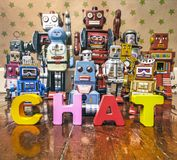 Chat bot robots. Chat Bot with wooden letters with retro robot toys on old woden floor Royalty Free Stock Photography