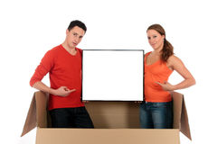 Chat box couple advertising. Young couple friends in chat box, cardboard box representing chat room holding advertising board.  Studio, white background Royalty Free Stock Photo