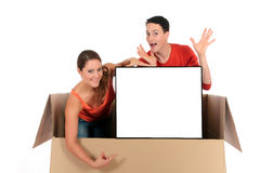 Chat box couple advertising. Young couple friends in chat box, cardboard box representing chat room holding advertising board.  Studio, white background Royalty Free Stock Image