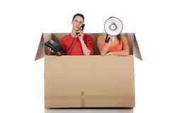 Chat box friends communication. Young couple friends in chat box, cardboard box representing chat room.  Studio, white background Royalty Free Stock Image