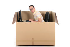 Chat box man computer. Young nerd, geek man having a chat session, chat box, cardboard box representing chat room.  Studio, white background Stock Photo