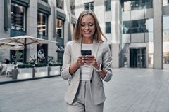 Chat with client. Beautiful young woman in suit using smart phone and smiling while standing outdoors stock images