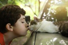 Chat de baiser de garçon d'adolescent s'étendant sur la voiture Photo libre de droits