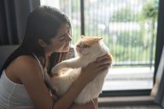 Chat exotique de shorthair de belle étreinte de femme Image libre de droits