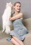 Chat heureux de fixation de femme tout en se reposant dans le divan Photos libres de droits