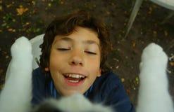 Chat heureux de prise de garçon d'adolescent de la fin d'arbre  Image stock