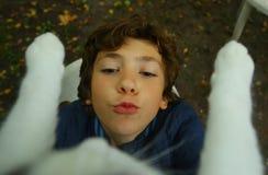 Chat heureux de prise de garçon d'adolescent de la fin d'arbre  Photo stock
