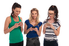 Chat mit drei glücklicher zufälliger Frauen an ihren Telefonen Stockfotografie