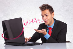 Chat, networking, love. Young man in suit sending his love to the person to whom is on a computer chat with Royalty Free Stock Images