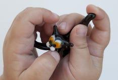 Chat noir en verre de jouet dans les mains d'un enfant en bas ?ge sur un fond blanc image libre de droits