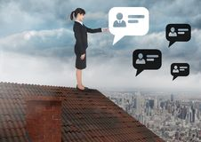 Chat profile bubbles and Businesswoman standing on Roof with chimney and cloudy city. Digital composite of Chat profile bubbles and Businesswoman standing on Stock Image