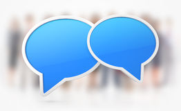 Chat or Speech symbols. Two clean blue speech bubbles on white background with blur people Stock Photos