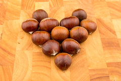 Chataîgnes de fruit saisonnier d'automne d'un plat en bois formé Image libre de droits