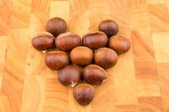 Chataîgnes de fruit saisonnier d'automne d'un plat en bois formé Images stock