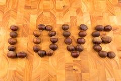 Chataîgnes de fruit saisonnier d'automne d'un plat en bois formé Photo stock