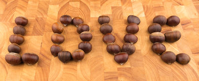 Chataîgnes de fruit saisonnier d'automne d'un plat en bois formé Photographie stock libre de droits