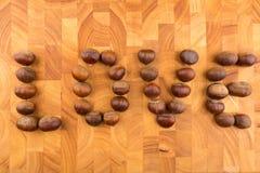 Chataîgnes de fruit saisonnier d'automne d'un plat en bois formé Photo libre de droits