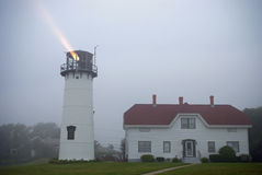Chatam Lighthouse. The Chatham Lighthouse on Cape Cod with light beam cutting through the evening fog Royalty Free Stock Photography