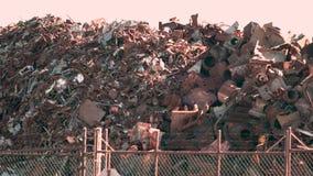 Chatarra oxidada en un montón a través de una cerca almacen de metraje de vídeo