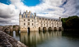 Chateau de Chenonceau over peaceful river waters. stock photography