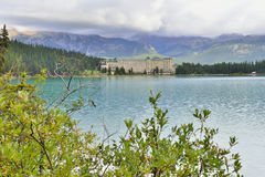 The Chateau Lake Louise hotel as seen from the trail in Canadian Rockies during a cloudy day Stock Photo