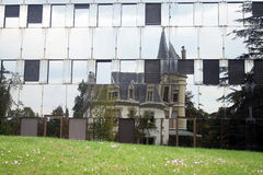Chateau reflected in office building. Reflection of an old chateau in the glass windows of a modern office building depicting cohabitation of the old ancient Stock Image