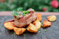 Chateaubriand steak and fried potatoes with bbq sauce and chopped parsley. Chateaubriand beef steak wrapped in bacon, fried potatoes with bbq sauce and parsley stock photography