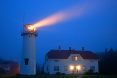 Chatham Lighthouse Cape Cod. The beacon of the Chatham Lighthouse shines brightly on a foggy evening royalty free stock photos