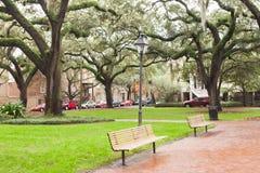 Chatham Square Historic District Savannah GA US. Green lawn and benches under oak trees on Chatham Square in Historic District of downtown city of Savannah Royalty Free Stock Photos
