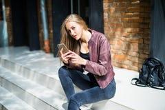 chating在智能手机的年轻美丽的微笑的适合的妇女,当基于台阶时 库存照片