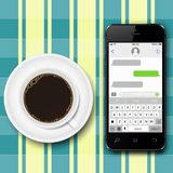 Chating and messaging concept. Smartphone with sms chat on screen and coffee cup on the tablecloth. Stock Photo